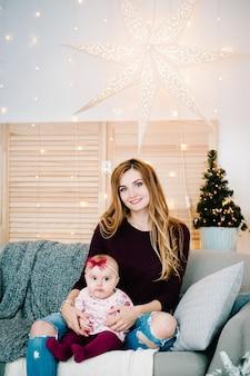 Bébé fille, fille avec maman sur le canapé près de l'arbre de noël. joyeux noël. intérieur décoré de noël. le concept de vacances en famille.