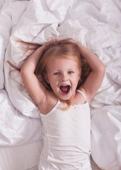 Bébé fille joue en pyjama sur le lit