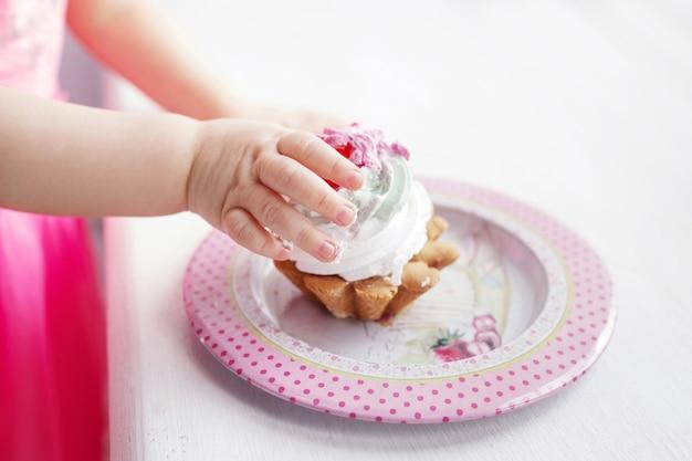 Bébé fille main tenant le premier gâteau d'anniversaire