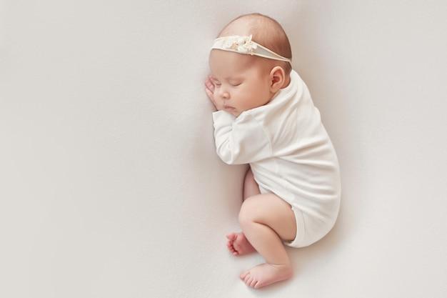 Bébé fille nouveau-née sur fond clair