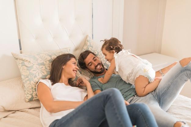 Bébé fille passe du temps avec ses parents au lit