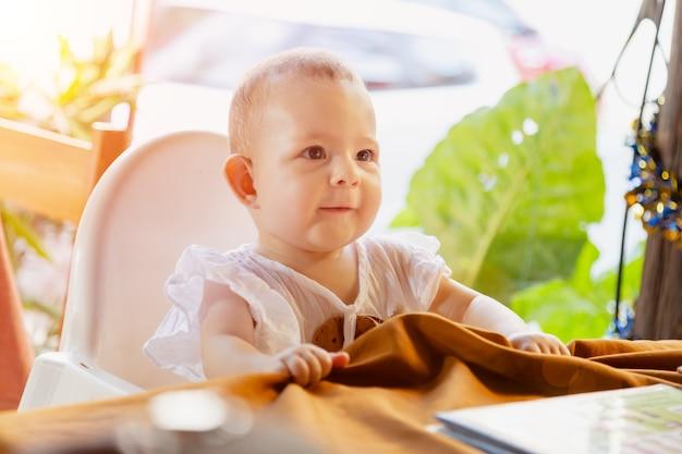 Bébé fille s'asseoir sur une chaise haute pour bébé dans un café de la rue tablebaby en robe barbote et tire la nappe