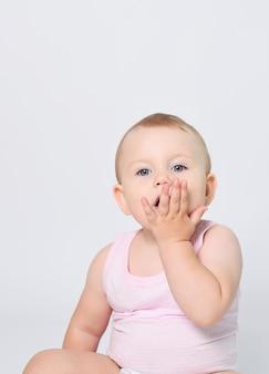 Un bébé sur fond blanc en culotte et un tshirt est heureux et souriant