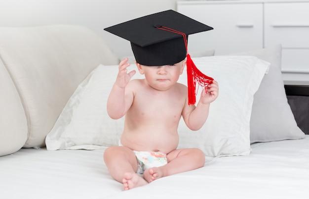 Bébé garçon de 10 mois en chapeau de graduation noir avec pompon