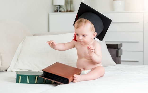 Bébé garçon de 10 mois en chapeau de mortier assis avec de gros livres