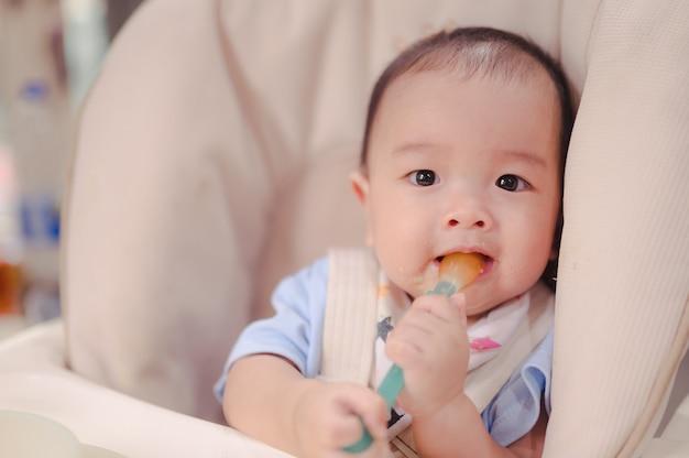 Bébé garçon asiatique mangeant des aliments mélangés avec une cuillère