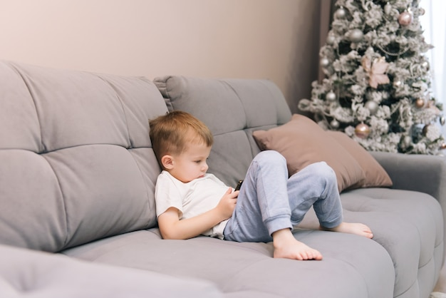 Bébé garçon assis sur le canapé avec un téléphone dans ses mains, la dépendance des enfants aux gadgets