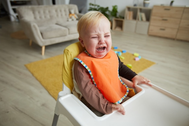 Bébé garçon assis dans une chaise bébé et pleurer dans la chambre
