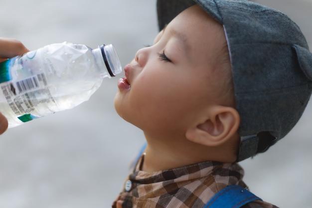 Bébé garçon buvant de l'eau que sa mère a fourni