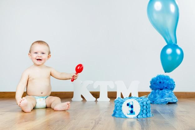 Bébé garçon célébrant son premier anniversaire avec gourmet cake and ba