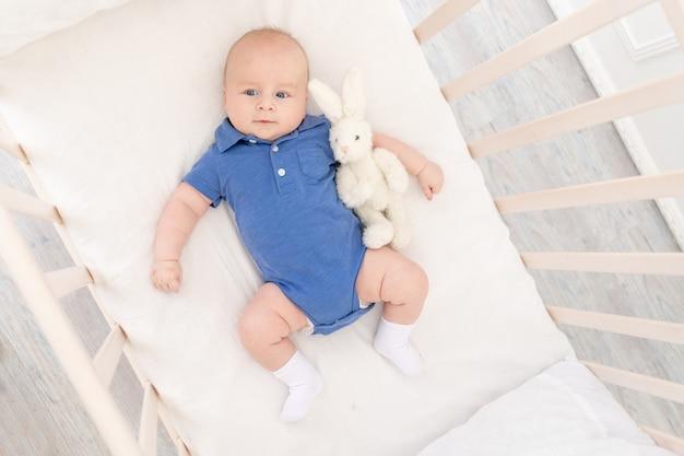 Bébé garçon dans un berceau se trouve sur le dos avec un jouet, un nouveau-né heureux se réveille