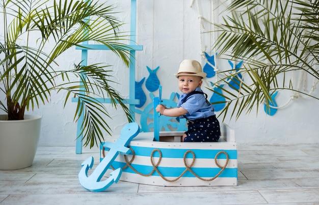 Bébé garçon dans un chapeau de paille est assis dans un bateau en bois blanc et bleu sur une surface blanche avec un espace pour le texte