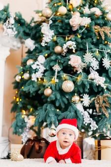 Bébé garçon dans un costume de père noël est allongé sur le ventre près d'un bel arbre de noël avec des guirlandes et des cadeaux