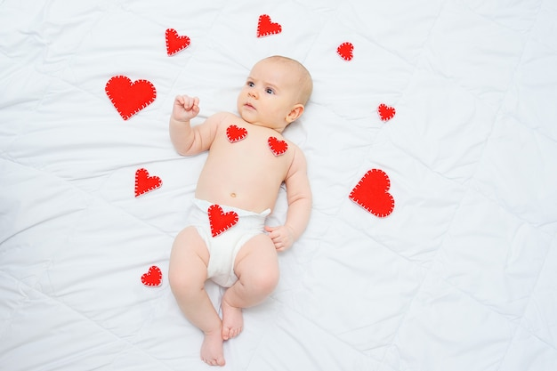 Bébé garçon dans une couche blanche se trouve contre les coeurs rouges aiment la saint-valentin