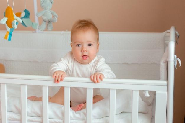 Bébé garçon dans la crèche dans la chambre des enfants