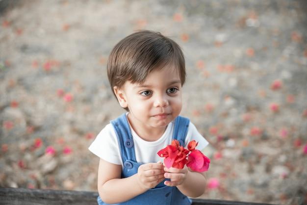 Bébé garçon mignon avec barboteuse dans le jardin sur le banc, tenant une fleur