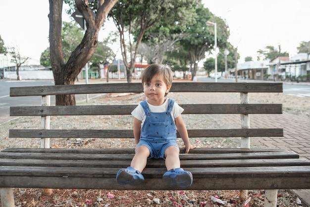 Bébé garçon mignon avec barboteuse dans le jardin sur le banc