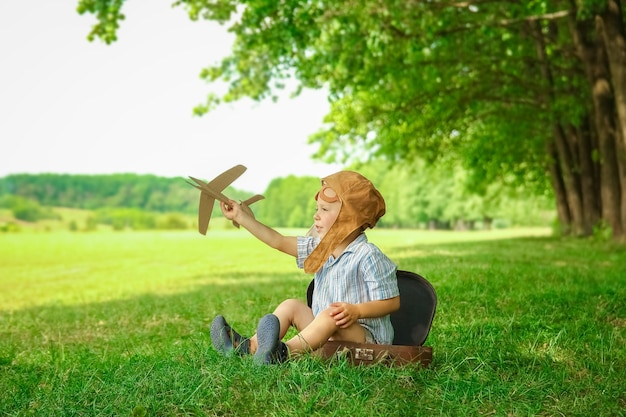 Un bébé garçon par l'avion joue sur la nature dans le parc. garçon en vacances pilote.