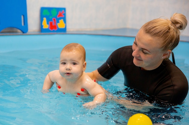 Bébé garçon s'entraîne à nager dans la piscine avec un entraîneur