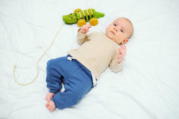 Bébé garçon se trouve sur un lit blanc à côté d'un jouet crocodile