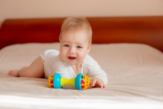 Bébé garçon se trouve sur le ventre avec un jouet sur le lit dans la chambre