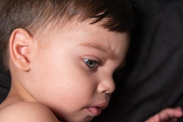 Bébé garçon sur tissu noir avec une lumière reflétant sur son visage