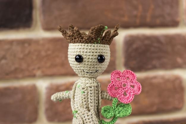 Bébé groot tricoté avec une fleur dans un pot sur fond de mur de briques. héros de bandes dessinées