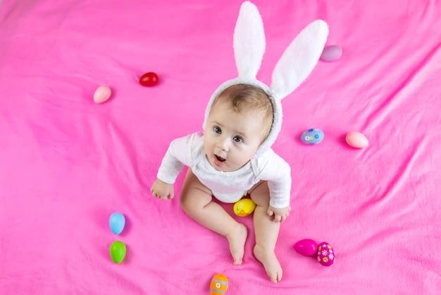 Bébé habillé comme un lapin avec des œufs de pâques pour les vacances de pâques