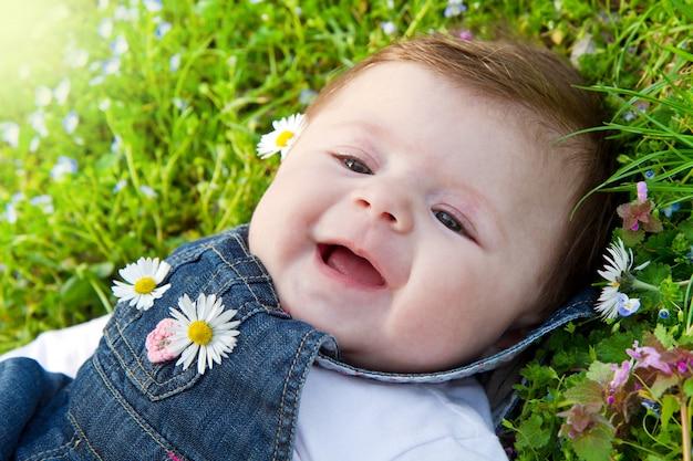 Bébé sur l'herbe verte avec marguerite