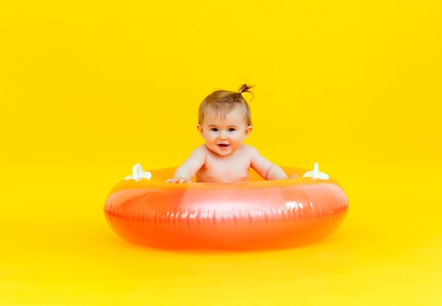 Un bébé heureux de 10 mois avec un cercle de natation est assis sur un fond jaune, photo en studio du bébé dans un cercle de natation