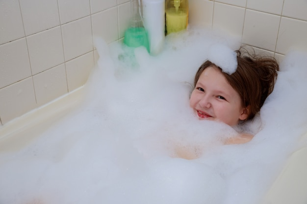 Bébé heureux dans le bain, nageant dans la douche en mousse.
