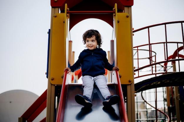 Bébé heureux mignon drôle jouant sur le terrain de jeu. l'émotion du bonheur, du plaisir, de la joie. sourire d'enfant.