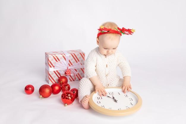 Bébé avec horloge, cadeau et boules de noël sur fond isolé blanc, espace pour le texte, le nouvel an et le concept de noël