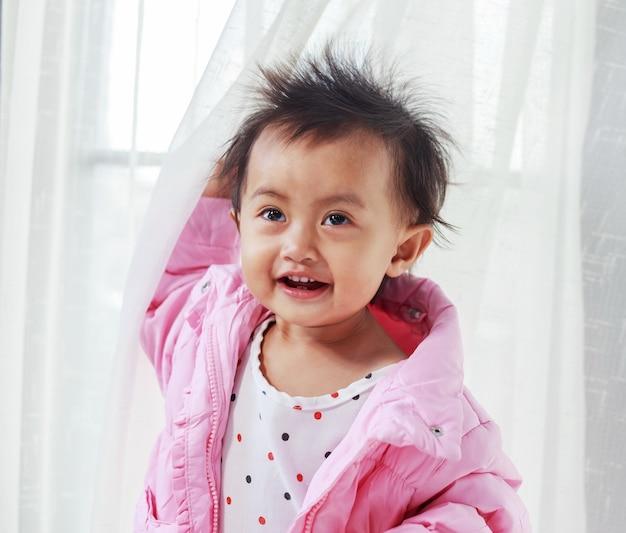 Bébé jouant à cache-cache derrière le rideau