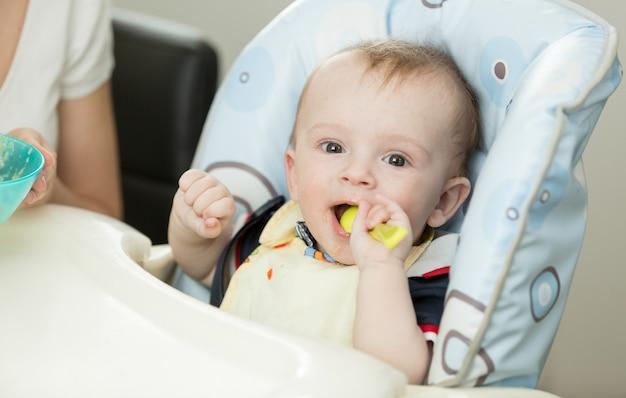 Bébé jouant avec une cuillère en mangeant