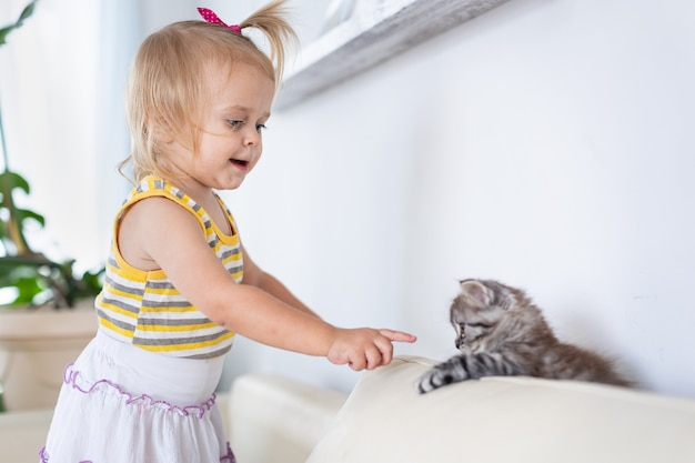 Bébé jouant avec un petit chaton sur le canapé