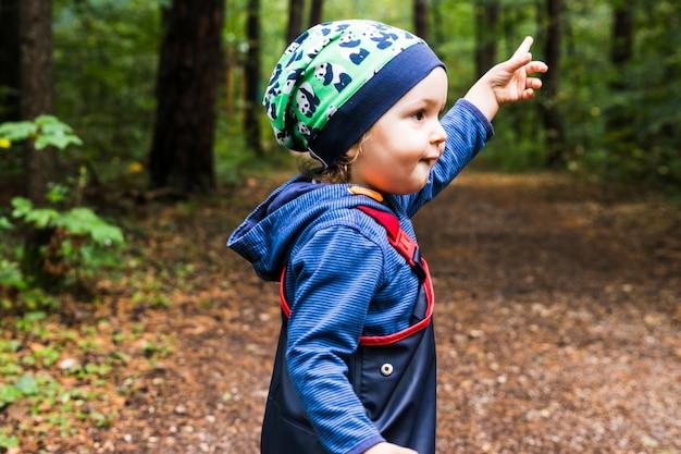 Bébé jouant sur un sentier forestier en automne