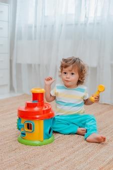 Bébé joue par terre dans la pièce avec des jouets en plastique éducatifs.