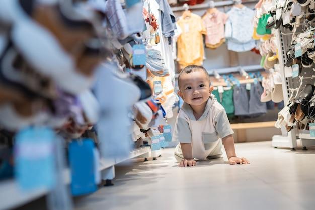 Bébé joue et rampe dans le magasin en faisant ses courses