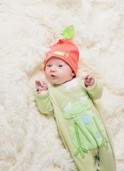 Bébé lilal au chapeau orange