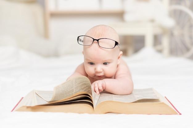 Bébé lisant un livre ou le regardant dans le concept de pépinière, d'apprentissage et de développement