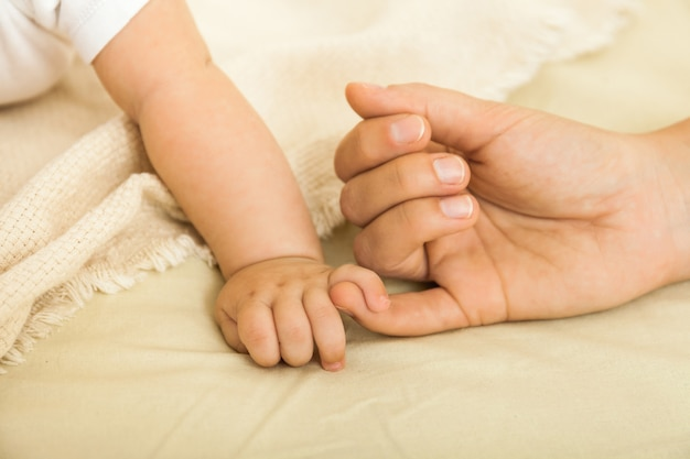 Bébé et les mains des mères se bouchent. concept de famille