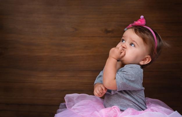 Bébé mange un cookie sur un fond en bois. enfant en robe rose sur fond de bois