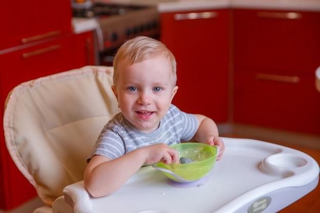 Bébé mange des flocons d'avoine. petit déjeuner bébé