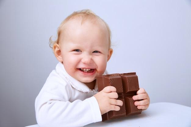 Bébé mange une grande barre de chocolat