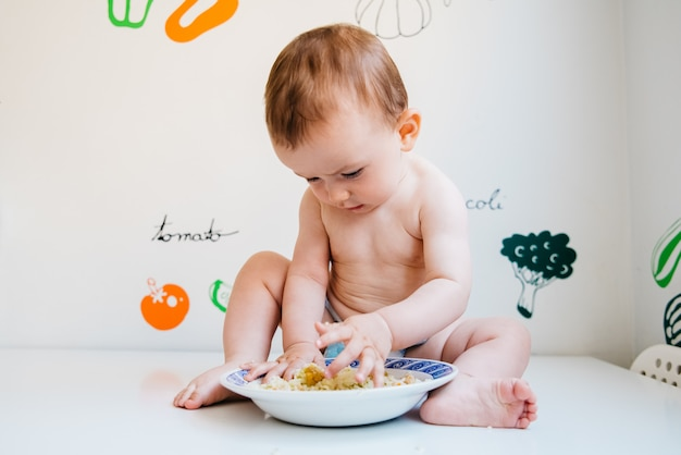Bébé mange seul apprenant par la méthode de sevrage dirigée par bébé