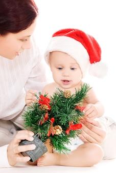 Bébé et mère avec des cadeaux de noël sur mur blanc