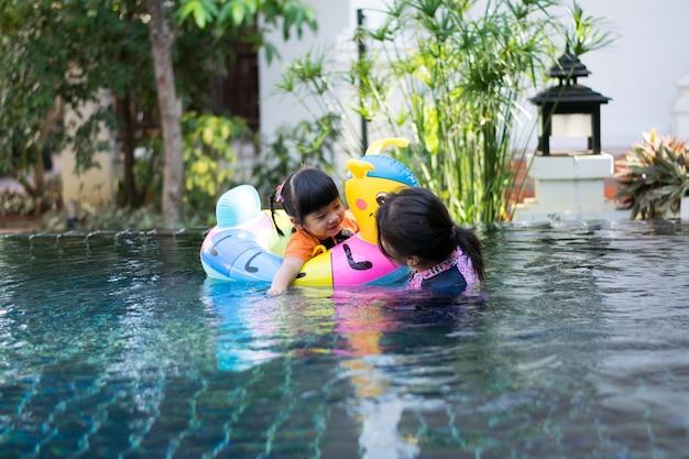 Bébé et mère jouant de l'eau dans la piscine