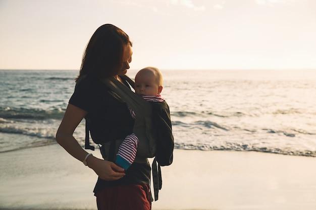Bébé et mère en mer au jour d'été. héhé marchant sur la nature à l'extérieur. enfant dans un sac à dos porteur. femme et son bébé sur l'océan littoral sur l'île de tenerife, espagne. voyager en europe