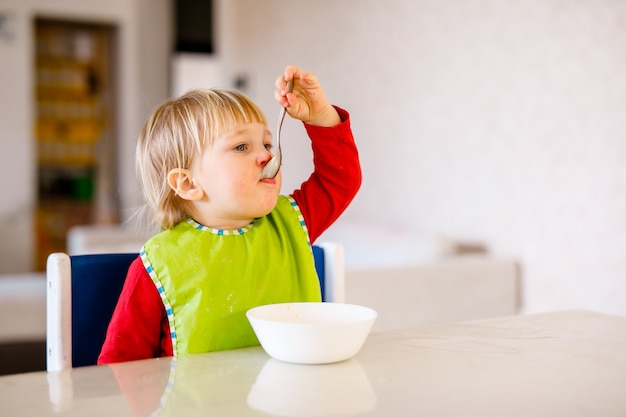 Bébé mignon assis sur une chaise haute pour enfants et manger des légumes seuls dans la cuisine blanche.